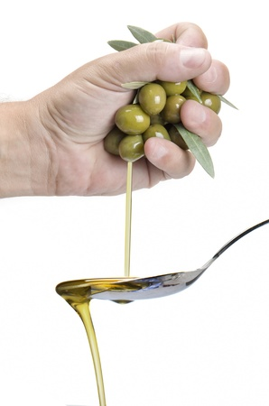 dropping: A hand squeezing olives and getting olive oil into a spoon.