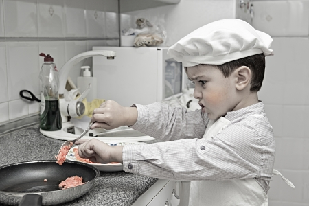 Child dressed as a chef working in the kitchen photo