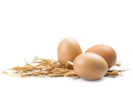 Verse eieren op wat stro geïsoleerd over een witte achtergrond Stockfoto