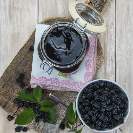 blackberries: A pot with blackberry jam and some fresh fruits and leaves