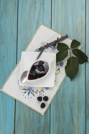 brambleberry: Un peque�o cuenco con mermelada de mora y algunas frutas frescas y hojas Foto de archivo