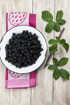 brambleberry: A bowl with ripe wild blackberries on an old wooden background Stock Photo