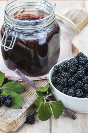 A pot with blackberry jam and some fresh fruits and leaves