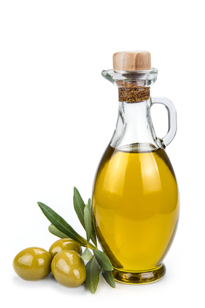 Olive oil in a glass bottle and green olives isolated over a white background