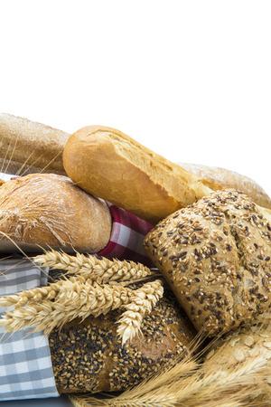 canasta de panes: Surtido del pan decorado con orejas de cereales y aislados en un fondo blanco
