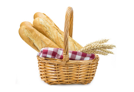 Basket with wheat bread and ears isolated over a white background photo
