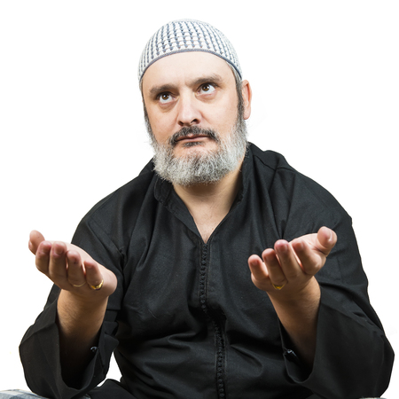 Muslim man in traditional dress praying over a white background. photo