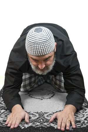 Muslim man in traditional dress praying over a white background.