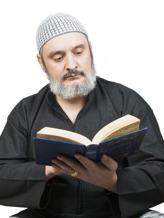 Muslim man in traditional dress reading the Koran. photo