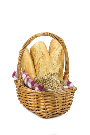 Basket with wheat bread and ears isolated over a white  photo