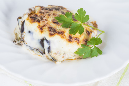 Traditional Greek moussaka served and decorated with a leaf of parsley photo