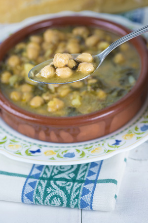 potage: Stew of chickpeas and spinach with cod on a  table with a tablecloth