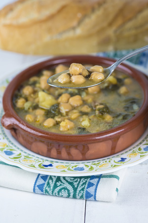winterly: Stew of chickpeas and spinach with cod on a  table with a tablecloth