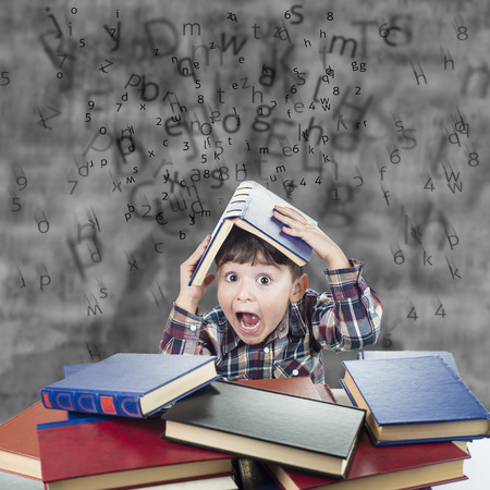 schoolwork: Child againts the rain of numbers and letters with a book over his head Stock Photo