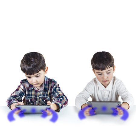 Twin brothers connected wirelessly and playing with a digital tablet. photo