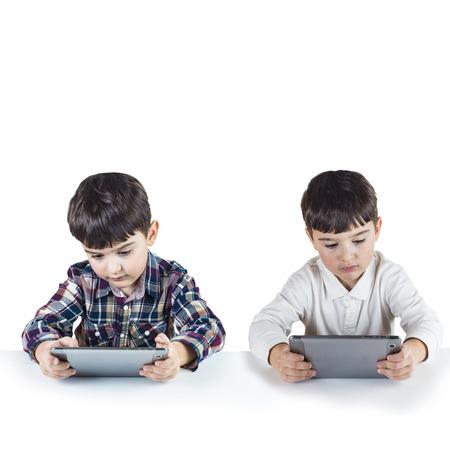 hermanos jugando: Hermanos gemelos conectados de forma inalámbrica y jugando con una tableta digital.