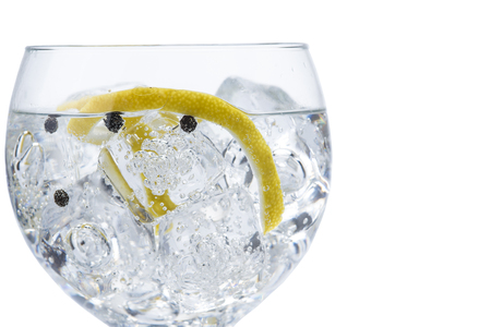 Gin and tonic in a balloon glass garnished with lemon and isolated over awhite background