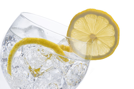 lemon wedge: Gin and tonic in a balloon glass garnished with lemon and isolated over awhite background