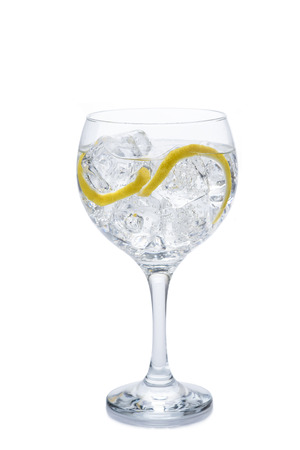 gin: Gin and tonic in a balloon glass garnished with lemon and isolated over awhite background