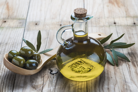 olive  oil: A glass bottle of olive oil and a wooden spoon with  olives on a table