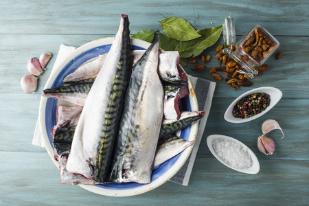 mackerel: A plate with fresh mackerel and spices on the kitchen table