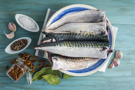 A plate with fresh mackerel and spices on the kitchen table
