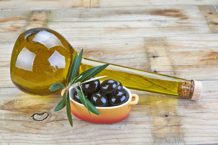 Premium olive oil and black olives on a wooden background photo