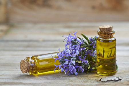 Rosemary essential oil in a small glass vial and plant with flowers on a wooden background Stock Photo