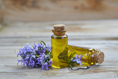 rosemary flower: Rosemary essential oil in a small glass vial and plant with flowers on a wooden background Stock Photo