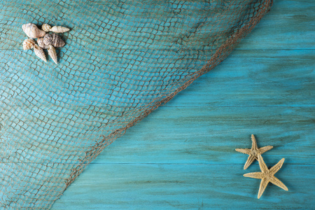 fishnets: Summer holidays in blue with fishing net ans seashells and a space for advertising