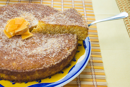 Homemade coconut and pumpkin cake on a yellow tablecloth photo