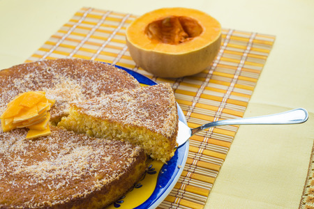 Homemade coconut and pumpkin cake on a yellow tablecloth Stock Photo