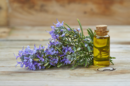 Rosemary essential oil in a small glass vial and plant with flowers on a wooden  Standard-Bild