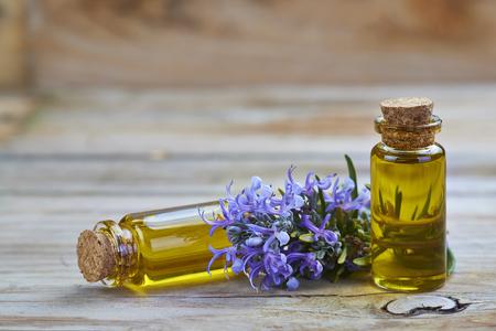 plantas medicinales: Aceite esencial de romero en un frasco pequeño de vidrio y plantas con flores en un de madera