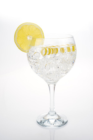 lemon wedge: Gin and tonic in a highball cup garnished with a lemon wedge and twist