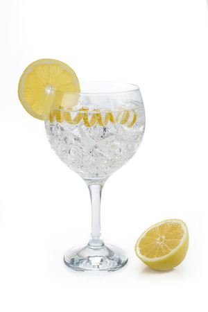 Gin and tonic in a highball cup garnished with a lemon wedge and twist