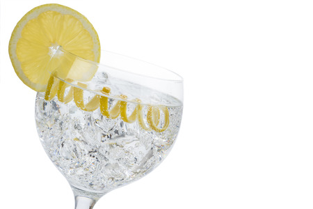 wedge: Gin and tonic in a highball cup garnished with a lemon wedge and twist