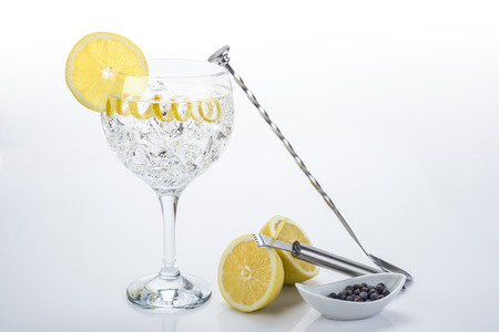 garnished: Gin and tonic in a highball cup garnished with a lemon wedge and twist