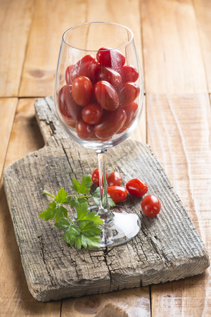 highball: Highball cup with grape tomatoes on a wooden  Stock Photo