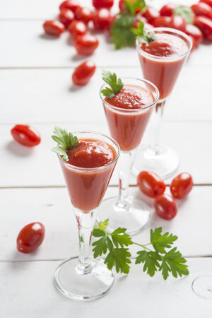 Tomato juice cocktails garnished with parsley leaves on a white wooden  photo