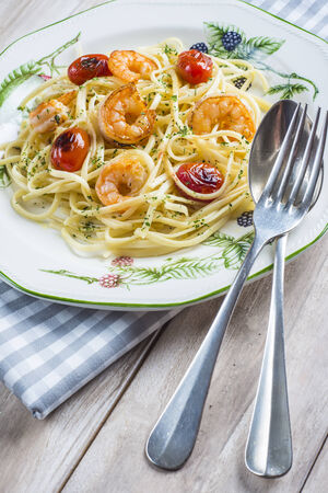 Spaghetti with prawns and grape tomatoes garnished with oregano and parsley photo