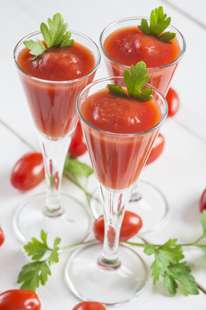 Tomato juice cocktails garnished with parsley leaves on a white wooden background and cherry tomatoes photo