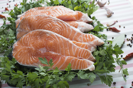 pink salmon: A platter with sliced fresh salmon and ingredients to cook it on the table of the kitchen Stock Photo