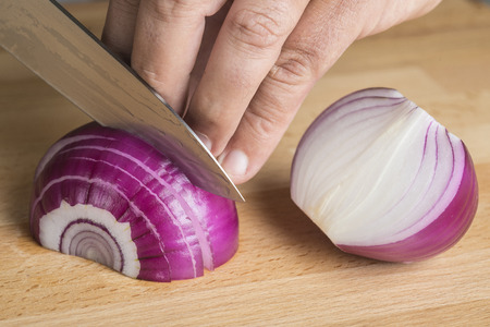 red onion: Chef choppig a red onion with a knife on the cutting board Stock Photo