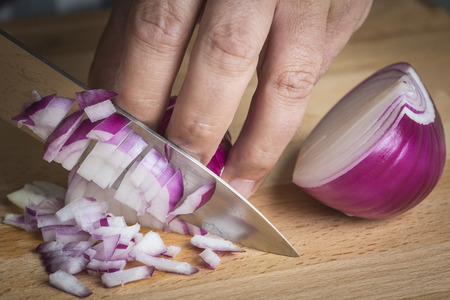 Chef choppig a red onion with a knife on the cutting board Standard-Bild