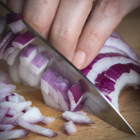 cutting vegetables: Chef choppig a red onion with a knife on the cutting board Stock Photo