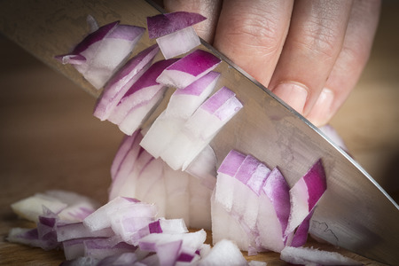 turda: Chef choppig a red onion with a knife on the cutting board Stock Photo
