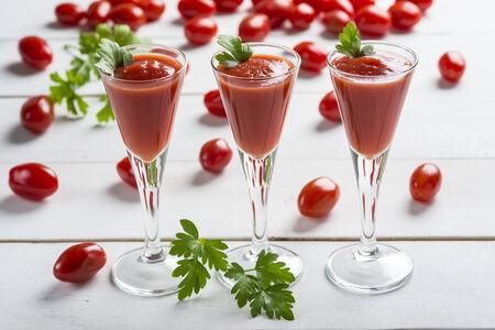 порно: Томатный сок коктейли с гарниром из листьев петрушки на белом фоне деревянных и помидорами черри Фото со стока