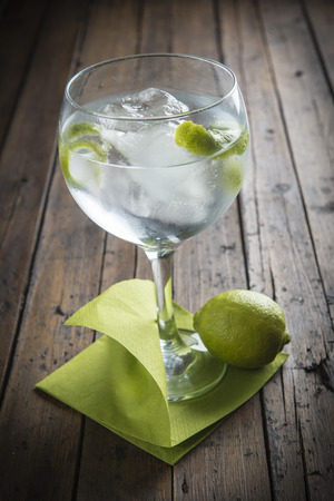 Gin and tonic garnished with lime on a wooden background photo