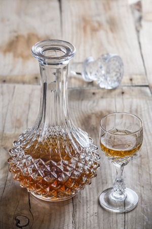 Crystal clear luxury glass bottle with liquor and a glass to serve photo